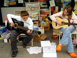The Dragon Kidz - Kevin and Friend Play Guitar to Raise Funds